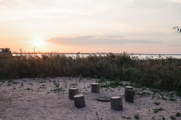 Open haard in de natuur, uitzicht op zee. voorbereiding voor een zomerfeest. zittend bij het vuur. kampvuur