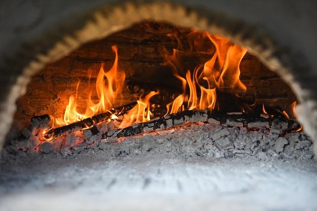Open haard met het fornuisbrand van de logboek houten brandende klei in huis in de winter - het concept van de open haardruimte