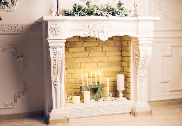 Open haard met kerstdecor en kaarsen op houten vloer