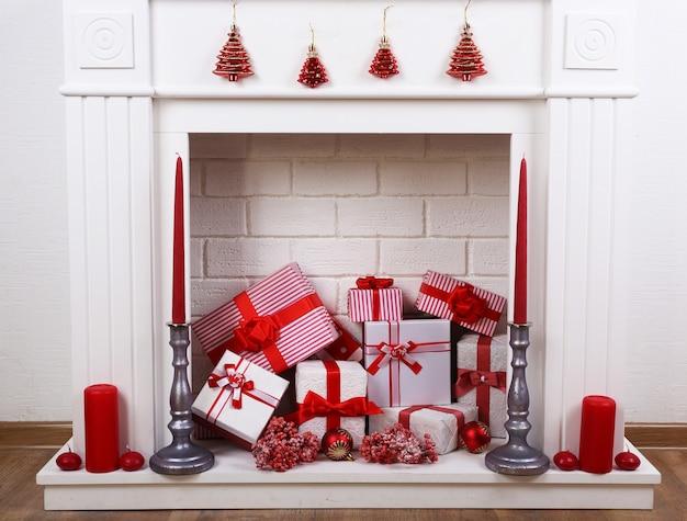 Open haard met kerstdozen en kaarsen op houten vloer