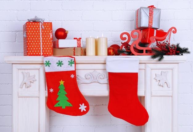 Open haard met kerstversiering op bakstenen muur achtergrond