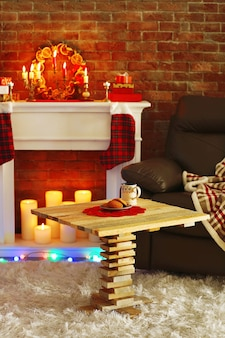 Open haard met prachtige kerstversieringen en houten tafel in comfortabele woonkamer