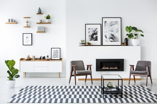 Open haard tussen grijze fauteuils in moderne woonkamer interieur met posters. echte foto