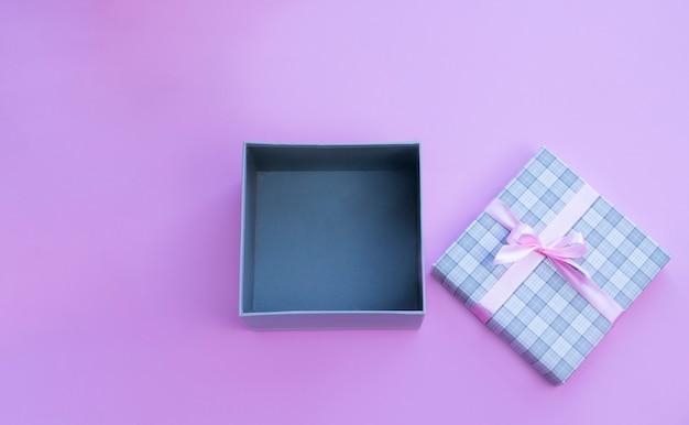 Open huidige doos met roze strik op roze achtergrond