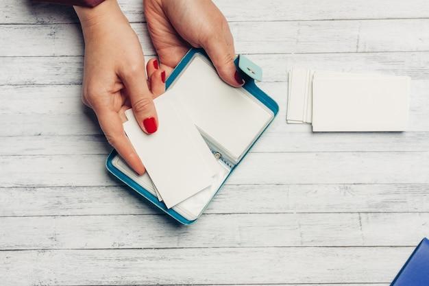 Open kaarthouder in vrouwelijke handen op een houten achtergrond bovenaanzicht