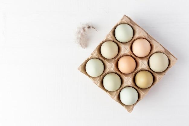 Open kartonnen doos met biologische eieren en veren op witte houten tafel