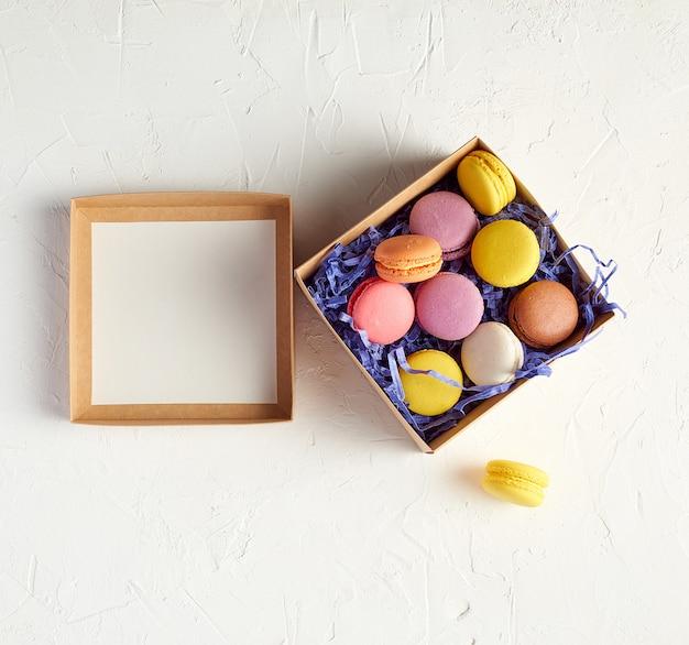 Open kartonnen doos met een gebakken dessert veelkleurige ronde macarons