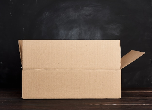 Open kartonnen doos staat op een bruine tafel