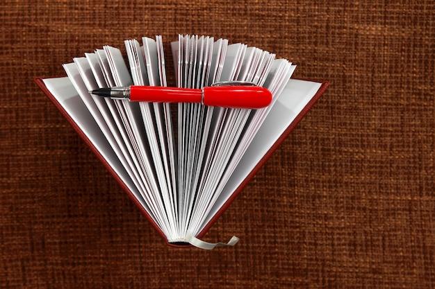 Open kladblok en rode pen close-up