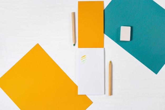 Open kladblok met gele papieren omslag en houten potlood voor tekenen, gum op wit bureau.