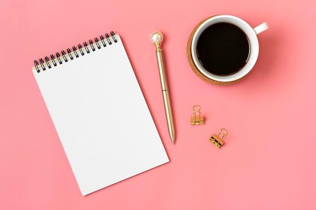 Open kladblok met kopje koffie en gouden pen