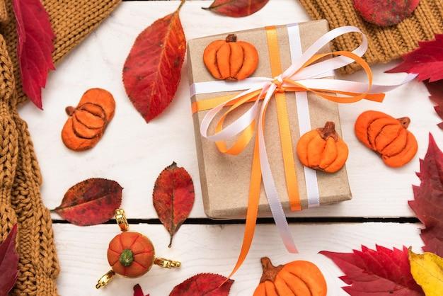 Open kladblok op tafel met herfstbladeren en pompoen.