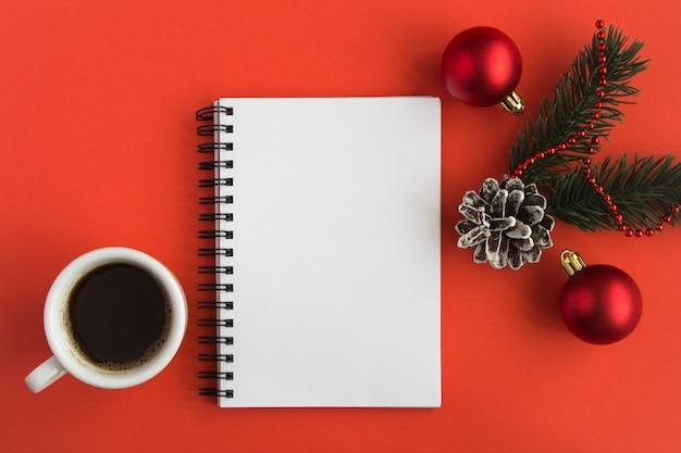 Open kladblok, zwarte koffie in de witte kop en kerst samenstelling op het rode oppervlak. kopieer ruimte. bovenaanzicht.