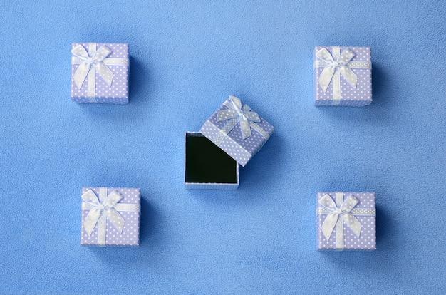 Open kleine geschenkdoos in blauw met een strikje op een deken van zacht en harig lichtblauw fleece.