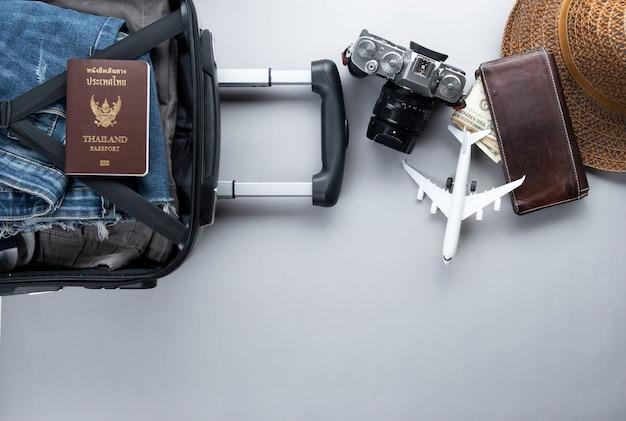 Open koffer die voor het reizen met het paspoort van thailand op grijze achtergrond wordt ingepakt
