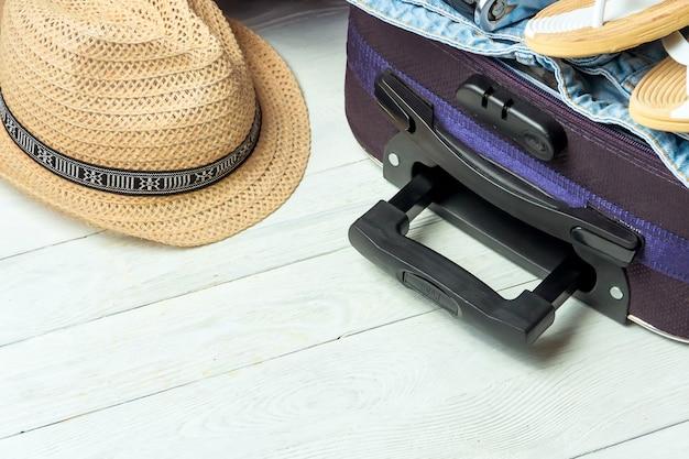 Open koffer met reistoebehoren op witte houten lijst met copyspace.