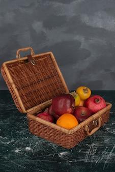 Open koffer vol fruit op marmeren oppervlak.