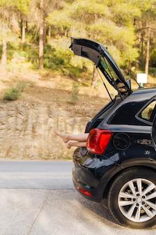 Open kofferbak van auto met vrouwenbenen