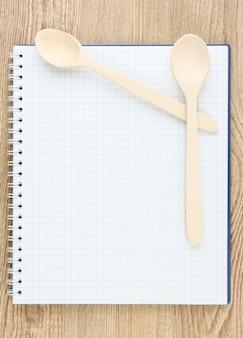 Open kookboek en keukengerei op houten