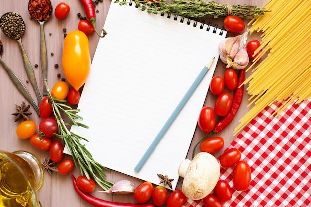 Open kookboek met tomaten, kruiden en specerijen