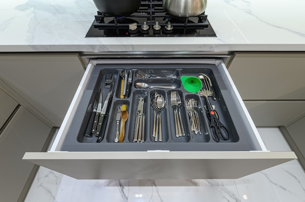 Open lade met bestek bij moderne witte woden keuken in klassieke stijl