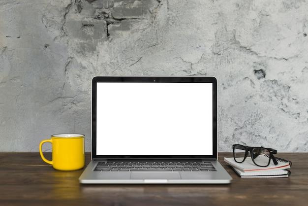 Open laptop; gele koffiemok; schouwspel; en dagboek op houten tafel met achtergrond van verweerde muur