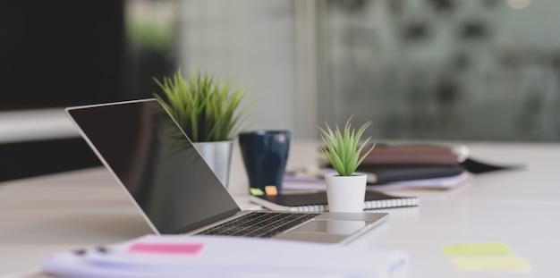 Open laptop met kantoorbenodigdheden en documenten op witte tafel in moderne kantoorstijl
