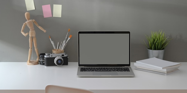 Open laptop met leeg scherm computer met vintage camera en kantoorbenodigdheden