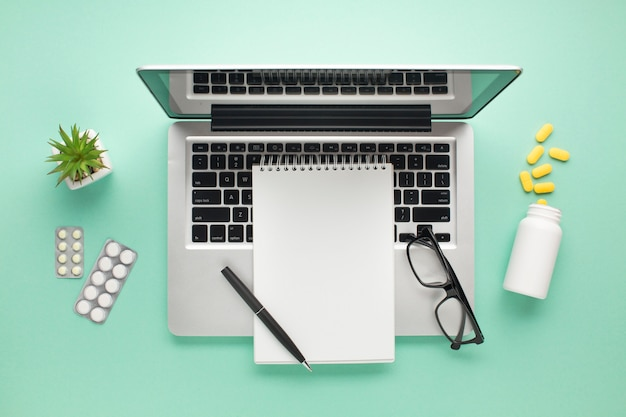 Open laptop met pillen en agenda op groen oppervlak