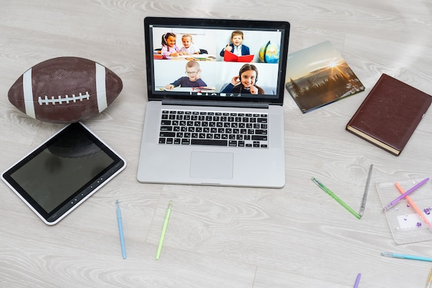 Open laptop met voetbal of rugbybal op de grond, videochat