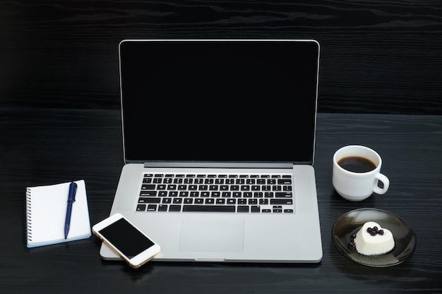 Open laptop, mok koffie, kladblok, smartphone en dessert