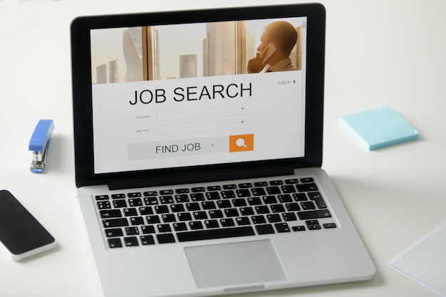 Open laptop op het bureau, job zoek titel op het scherm