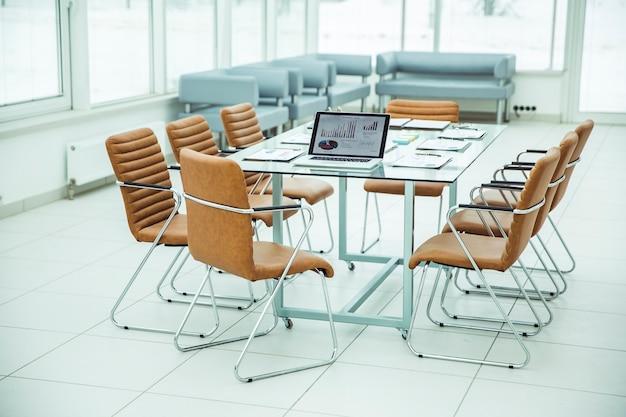 Open laptopcomputer met financiële grafieken en papieren verspreid op het bureaublad voordat zakelijke onderhandelingen worden gestart. de foto is een lege ruimte voor uw tekst