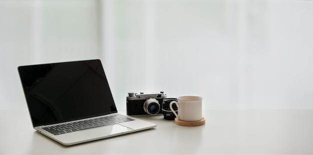 Open laptopcomputer met koffiekopje en vintage camera op witte tafel