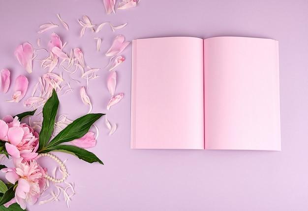 Open leeg notitieboekje met roze bladen en bloeiende pioenen