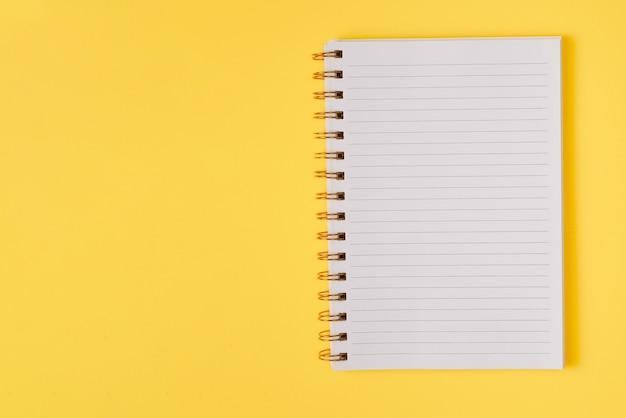 Open leeg notitieboekje op een gele achtergrond. bovenaanzicht. ruimte voor tekst of ontwerp.