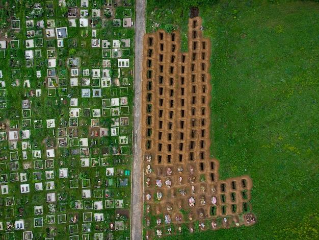 Open lege graven tussen het groene gazon, luchtfoto drone uitzicht op lege graven.