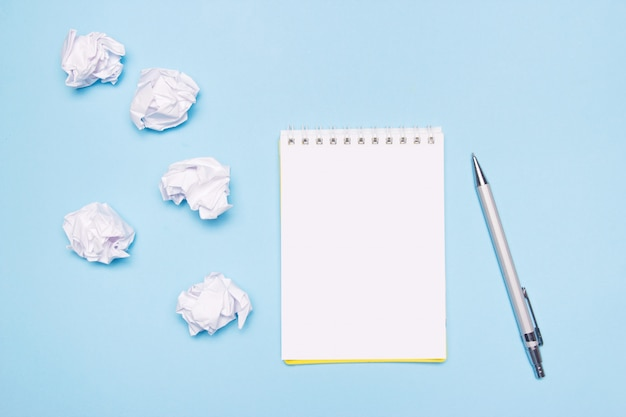 Open lege notebook, pen en verfrommeld papier ballen op blauw papier