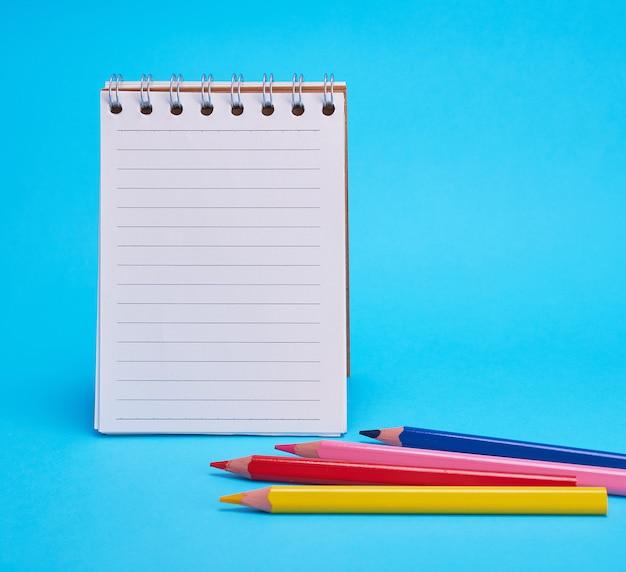 Open lege notitieblok in de rij en veelkleurige houten potloden
