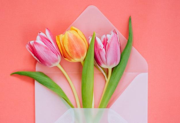 Open mat transparante envelop met veelkleurige tulpen op levende koraal achtergrond