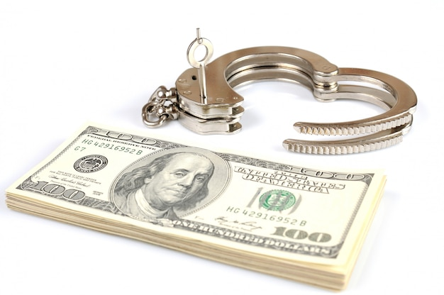 Open metalen handboeien, sleutels en stapel amerikaanse dollars contant