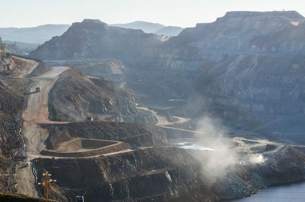 Open mijnen met het stof van de machines aan het werk