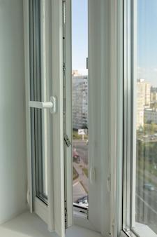 Open modern pvc-venster op de achtergrond van flatgebouwen met meerdere verdiepingen