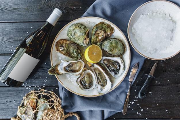 Open natte oesters op een bord met citroen