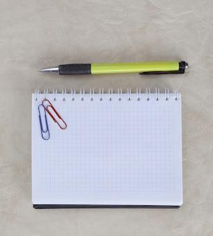 Open notebook paperclip en pen op papier backgroundphoto met kopie ruimte