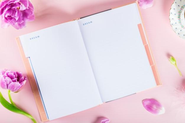 Open notebook voor het schrijven van dromen en ideeën met bloemen in de buurt