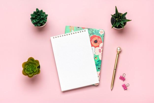 Open notitieblok vetplanten gouden pen op roze achtergrond spiraal notebook op tafel business planning edu...