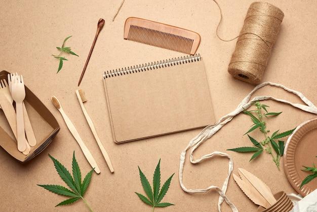 Open notitieboek met lege vellen, een stoffen tas en wegwerpservies van bruin kraftpapier, groene hennepbladeren