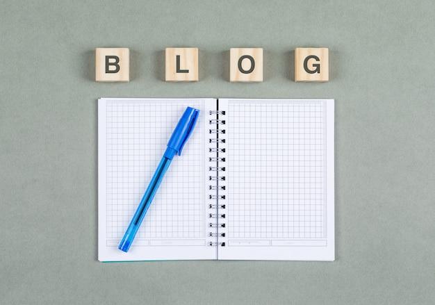 Open notitieboekje en het nemen van notaconcept met pen, houten blokken op grijze hoogste mening als achtergrond. ruimte voor tekst. horizontaal beeld