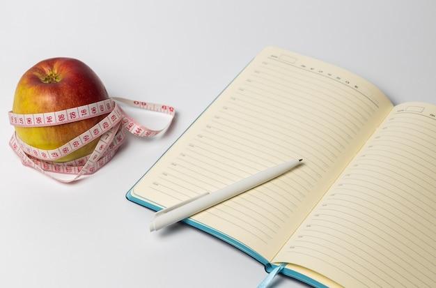 Open notitieboekje met een appel en een centimeter op tafel.